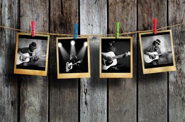 Guitarist photo hanging on clothesline on wood background.