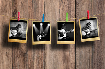 Guitarist photo hanging on clothesline on wood background.