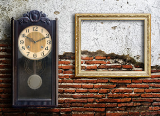 Old clock and empty picture frame on wood wall.