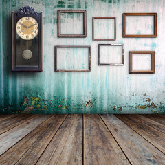 Old clock and empty picture frame in old room.