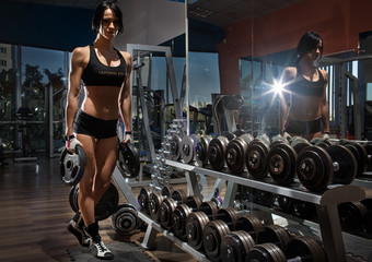 Gym.Sporty girl posing with dumbbells