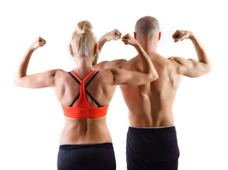 Athletic middle-age man and woman posing in studio. Back view.