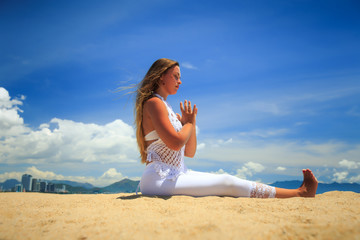 blonde girl in lace closed eyes sits in yoga asana