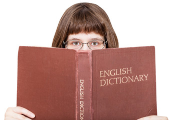 girl with spectacles looks over English Dictionary