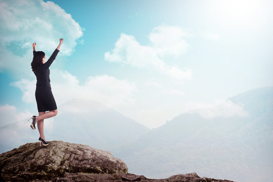 Asian business woman standing on the top of the mountain