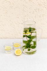 Außenaufnahme, Karaffe mit Wasser, das mit Minze und Zitrone ar