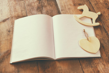 open blank notebook and wooden rocking horse toy over wooden table