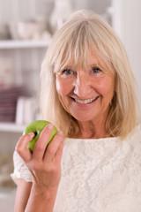 Frau Senior ist einen Apfel mit Freude