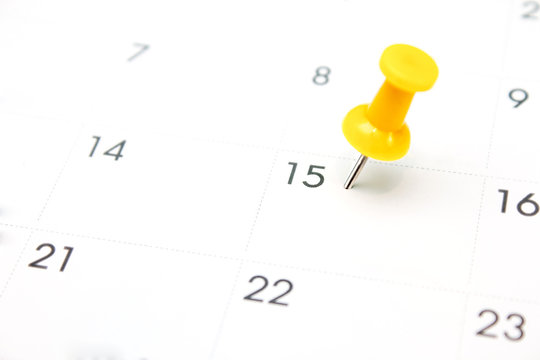 Yellow pin on White Calendar Closeup shot