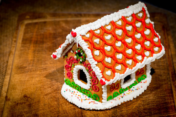 beautifully decorated gingerbread house stands on a wooden table