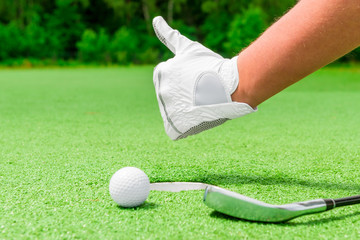 closeup hand in a white glove and a ball near the hole