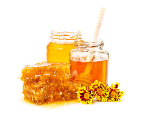 Sweet honeycomb and two jars of honey with stick and flowers