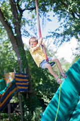 Cute child, boy, rides on Flying Fox play equipment in a childre