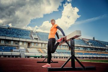 Slim blond female in sportswear doing exercises.