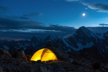 Twilight Mountain Panorama and Tent Illuminated Camping Yellow Tent Night High Altitude Alpine Landscape Shining Moon in Dark Blue Sky cooler tone