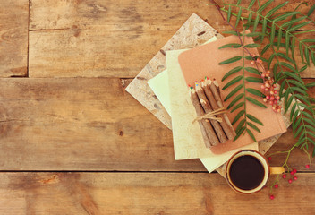 vintage notebook, old paper and stuck of colorful wooden pencil next to cup of coffee