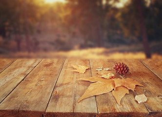 autumn background of fallen leaves over wooden table and forest backgrond