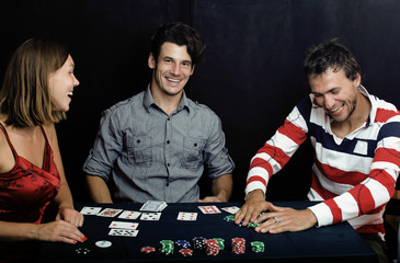 young people playing poker on black background