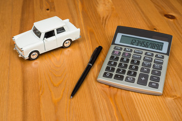 Toy car and calculator concept for buying, renting, fuel or service and repair costs