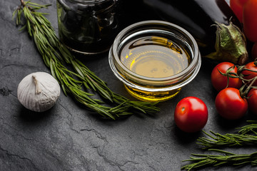 Olive oil with different vegetables and rosemary on the black stone table