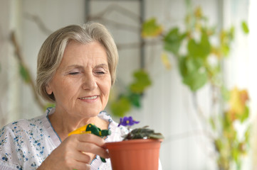 Senior woman watering flower