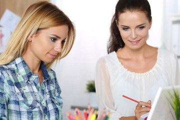 Two female designers in office looking at laptop computer