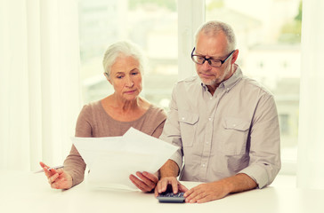 senior couple with papers and calculator at home