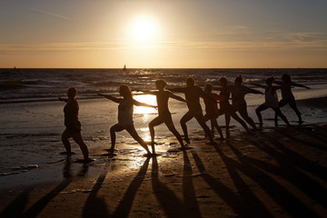 beach yoga in group by the sea at sunset