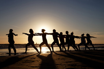yoga at sunset in group by the sea