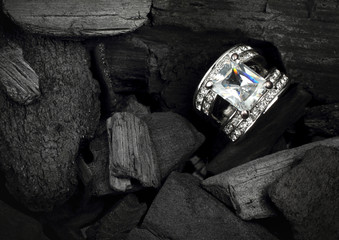 jewelry ring witht big colourful diamond on black coal backgroun