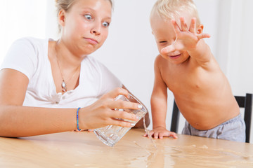 Older sister with her younger brother at the table playing with glass of water