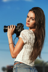 cute young female photographer with camera outdoors
