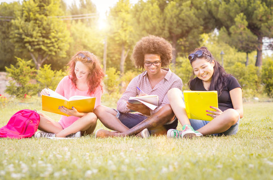 three students studying and laughing in the park - people, lifestyle and nature concept