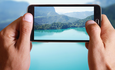 Male hand taking photo of a lake with green mountains landscape with cell, mobile phone.