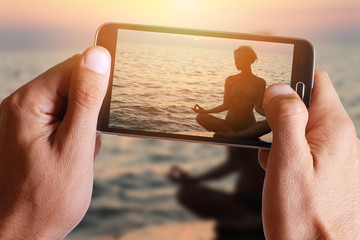 Male hand taking photo of Yoga woman meditatiing in lotus pose on the beach during sunset with cell, mobile phone.