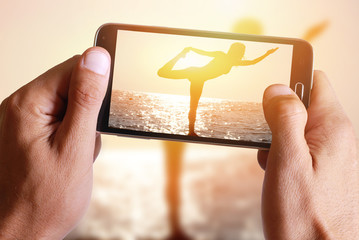 Male hand taking photo of Silhouette of young woman practicing yoga on the beach near the sea, ocean at sunset with cell, mobile phone.