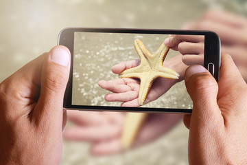 Male hand taking photo of sea star in little boy, child hand with cell, mobile phone.