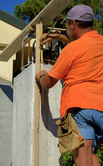 worker with pencil and  folding ruler wooden meter track a measurement on a concrete pillar