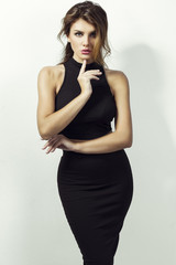 Brunette girl in black skirt  and crop top isolated on white. perfect body and make up.