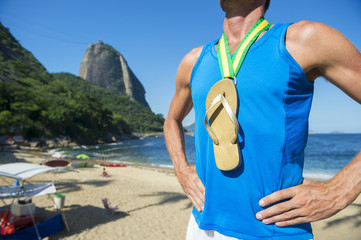 Champion athlete wearing gold medal flip flop celebrating at Red Beach Rio de Janeiro Brazil