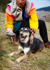 Woman brushing her dog in spring meadows. Smiling Dog