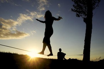 woman balancing in slack line , slacklining , and man looks at him
