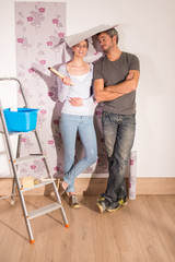 cheerful couple posing wallpaper on the walls of his apartment