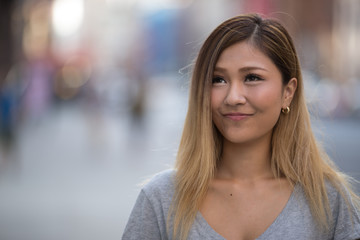 Young Asian woman in city smile happy face portrait