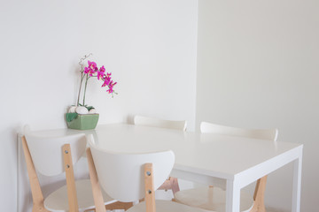 White empty dinning table set with chairs.