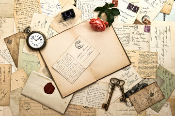 Open book, roses flower, old accessories and postcards