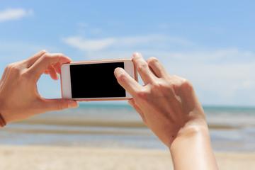 Using smart phone take photo at beautiful beach of Thailand.