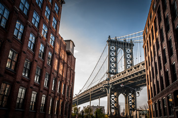 Foto auf Acrylglas Schmale Gasse Manhattan bridge seen from a narrow alley enclosed by two brick buildings on a sunny day in summer
