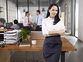 portrait of young asian business woman standing in office arms crossed