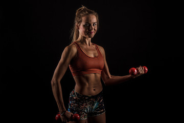 Fit woman holding weights over a dark background